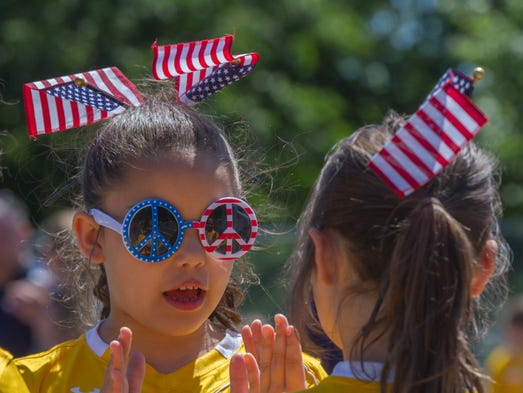 Kennedy Miller, 8, of the Monmouth United Soccer Club plays a clapping game with a team mate as they await the start of the Middletown 350 Parade in Middletown, NJ  on June 21, 2013 in Brick NJ.    Peter Ackerman / Staff Photographer