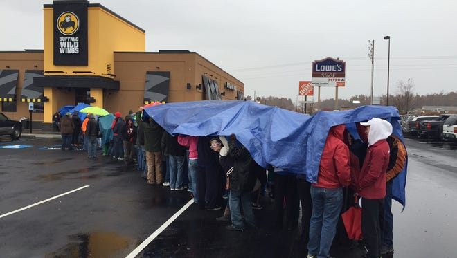 Customers, standing under tarps and umbrellas, line up awaiting the opening of the new Buffalo Wild Wings in Mountain Home on Saturday morning.