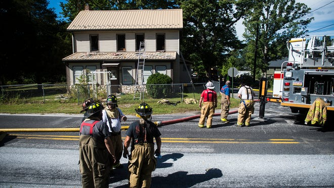 Firefighters work at the scene of a residential fire at 10 Fleshman Mill Rd in Oxford Township on Sunday.