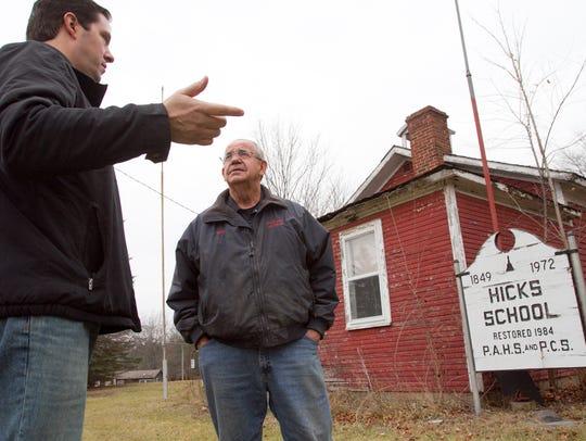 Brighton Township resident Tim Bennett, left, talks