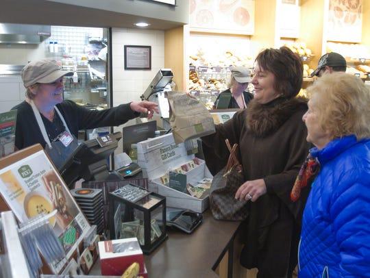 Panera Bread bakery cashier Vickie Davis gives an order
