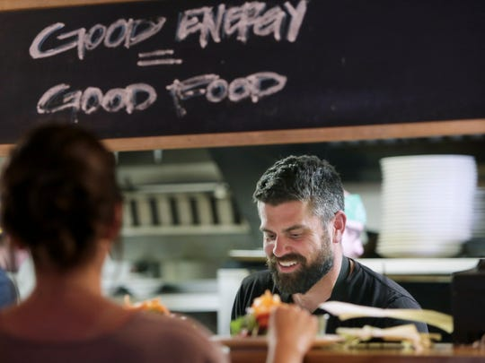In this June 1, 2017 photo, Luke Zahm prepares food for customers at his restaurant Driftless Cafe in Viroqua. This small town about two hours northwest of Madison is helping put Wisconsin on the culinary map.