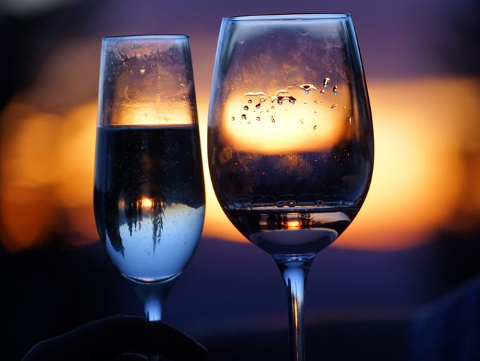 Trees reflect upside down in glasses of wine at sunset.