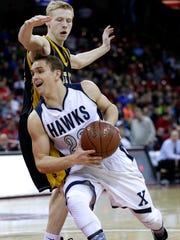 Xavier's Sam Burkart drives against East Troy's Connor Mitchell during Friday's WIAA Division 3 boys' state basketball semifinal at the Kohl Center in Madison.