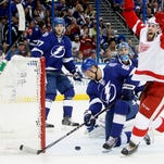 Tampa Bay Lightning's Anton Stralman (6) remains down along with goalie Ben Bishop (30) as Victor Hedman (77) watches as the puck bounces back out of the net with Detroit Red Wings center Landon Ferraro (29) celebrating a Red Wings rebound goal scored by Drew Miller during the second period of Game 5 of a first-round NHL hockey playoff series, Saturday.