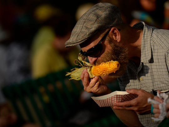 Ross La Haye, of Green Bay, enjoys red curry sweet corn during Taste On Broadway in downtown Green Bay on Aug. 7, 2014.
