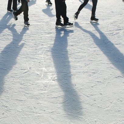 People cast a shadow as the skate at the WinterFest