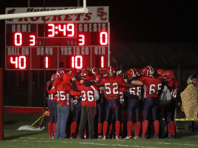 The Spencer/Columbus team huddles near the scoreboard
