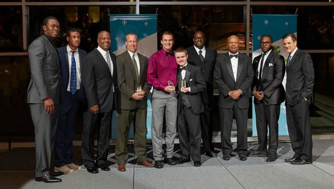 The 2015 Autism Alliance of Michigan's Courage Award was presented to Coach Jerry Van Havel, Jarrett Van Havel and Jay Granger by Detroit Lions defensive end Ziggy Ansah (from left), RJ Peete, former NFL quarterback Rodney Peete, former Detroit Lions offensive lineman Scott Conover, Detroit Lions head coach Jim Caldwell, Detroit Lions running back Joique Bell, and WJBK-TV Fox 2 Detroit sports anchor (and Detroit Lions Radio Network play-by-play announcer) Dan Miller.