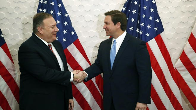 In this Jan.23, 2020 file photo, Secretary of State Mike Pompeo, left, and Florida Gov. Ron DeSantis pose for a photo before participating in a roundtable discussion with Venezuelan exiles, in Miami. While President Donald Trump deals with his high-profile political difficulties in his high-profile ways, his Cabinet heads are fanning out to battleground states in November's presidential vote, trying to assure essential support blocs on all that the Trump administration is doing for them.