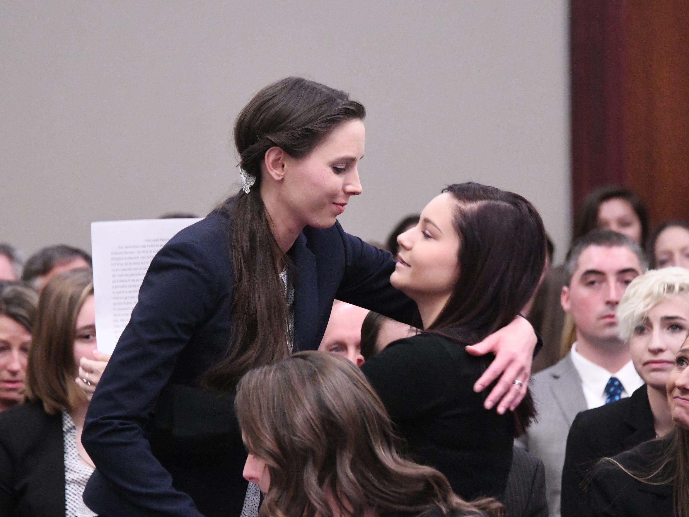 Rachael DenHollander hugs fellow Nassar victim Kaylee Lorincz after Lorincz's victim impact statement, before making her own.