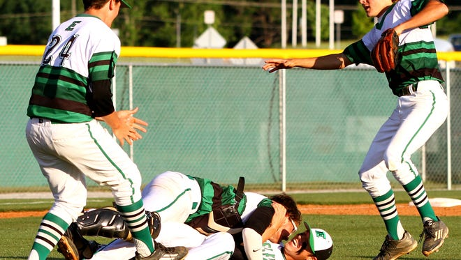 Easley's Holden Martin is tackled by teammates after throwing the last pitch in the Green Wave's 5-0 win over Nation Ford in the Class AAAA District II championship game Wednesday night.