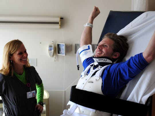 Jan. 6: Jim Harris stretches his arms during physical therapy with Drake Center therapist Cori West. The next day he flew to Craig Hospital in Denver, Colorado.