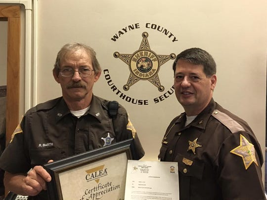 Deputy Rick Barth is honored by Sheriff Jeff Cappa for his work in the sheriff's department's re-accreditation process.