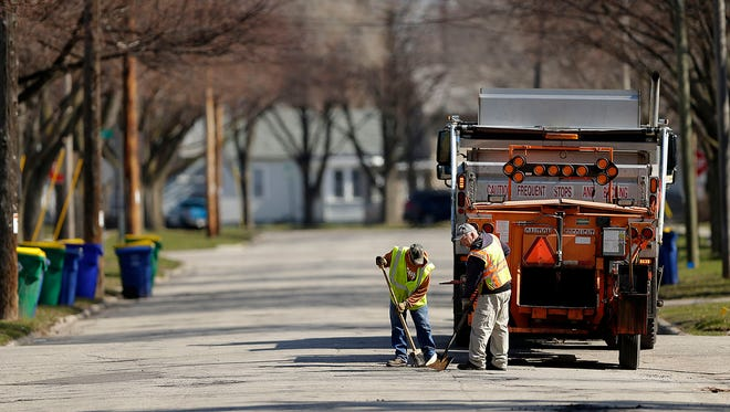 Tom Krueger, right, and Ray Magley, with the Green Bay Department of Public Works, fill in potholes along Roosevelt Street in Green Bay. Repaving the worst of the city's roads would cost $30 million.
