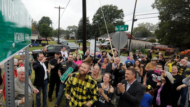 People, including Jacob and Destiny Chamberlin, center, react after the Noah Chamberlin Memorial Highway sign was revealed in Pinson, Tenn., on Friday, Oct. 14, 2016.