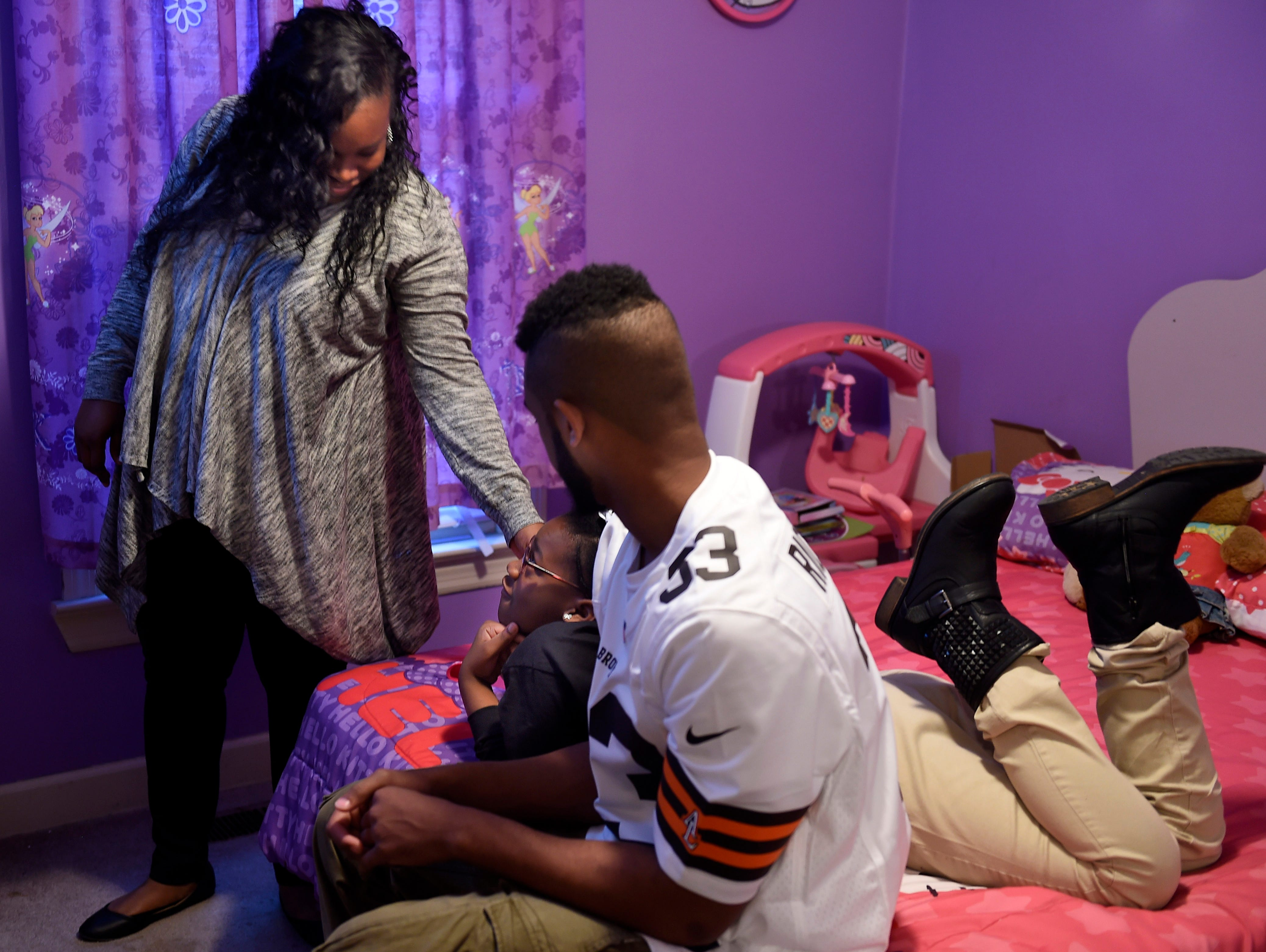 Vanessa Cortner checks on her daughter Nakia and young cousin Denarius Cortner as they watch cartoons together before heading off to school at their home Tuesday Feb. 2, 2016, in Nashville, Tenn. The East Nashville High School football player Denarius Cortner is committing to the Western Carolina football program.