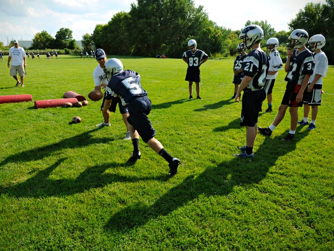 Coaches run Eden Valley-Watkins football players through drills during practice.