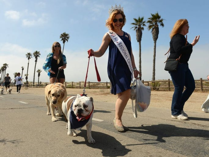 KAREN QUINCY LOBERG/THE STAR Gustavo leads Kristin Routh, Ms. America Regional California 2016, in a fundraising walk Sunday at San Buenaventura Beach at the Pooch Parade in Ventura, which was organized by the Canine Adoption and Rescue League.