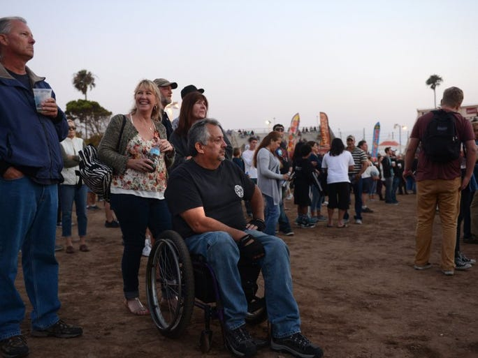 KAREN QUINCY LOBERG/THE STAR Javier Avila (seated), of Ojai, awaits the band Styx with his friends on Thursday night at the Ventura County Fair in Ventura.