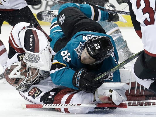 San Jose Sharks right wing Melker Karlsson, from Sweden, top, crashes into Arizona Coyotes goaltender Scott Wedgewood during the second period of an NHL hockey game in San Jose, Calif., Tuesday, Feb. 13, 2018. (AP Photo/Jeff Chiu)