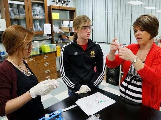 Abi Bymaster, right, instructs Emily Nettesheim, from left, and Caitlinn Lineback in a lab process for purifying a protein recently at McCutcheon High School.