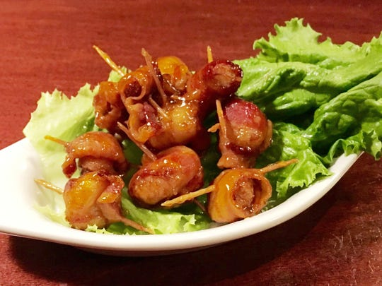 Rolled water chestnuts wrapped in bacon with homemade sweet-and-sour sauce from Rupp's in Cleveland.