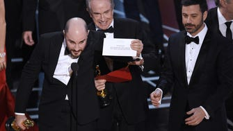 "Jordan Horowitz, producer of ""La La Land,"" shows the envelope revealing ""Moonlight"" as the true winner of best picture at the Oscars on Sunday, Feb. 26, 2017, at the Dolby Theatre in Los Angeles. Presenter Warren Beatty and host Jimmy Kimmel look on from right. (Photo by Chris Pizzello/Invision/AP) ORG XMIT: CADA418"