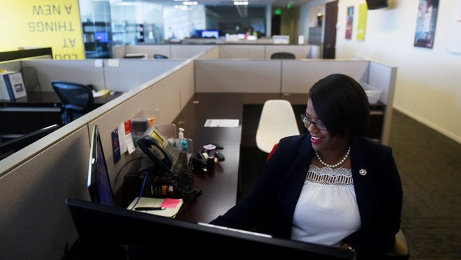 """Alethia Stafford, wife, mother of five and Navy veteran, works at her desk in West Palm Beach on Nov. 8, 2017, as a project coordinator for Suffolk Construction. Stafford credits her upbringing and time in the military for her success after her service. """"Growing up in a very firm, strict environment, your way is kind of paved for you and I feel that my life was planned to go the route of being in the military,"""" Stafford said. """"Had I not had that foundation as a child, I don't know that I would have liked the Navy very much. At first, you don't realize that you are learning life principles in the military until you actually get out and put them to use."""""""