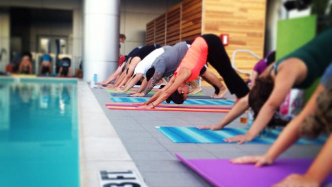 Visitors do outdoor yoga at Lustre Rooftop Bar.