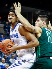 University of Memphis forward Dedric Lawson (left) drives to the basket against Tulane University defender Sammis Reyes (right) during first-half action at the FedExForum.