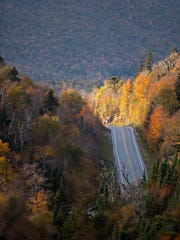 Sunlight illuminates a row of trees over Vermont Highway 17 as the state route nears the Appalachian Gap on Sunday, Oct. 5, 2014.