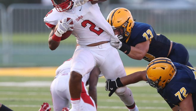 Canton's Markus Sanders is tackled by Dearborn Fordson's Saleh Homayed and Hussin Berro during first half Friday at Wayne State.