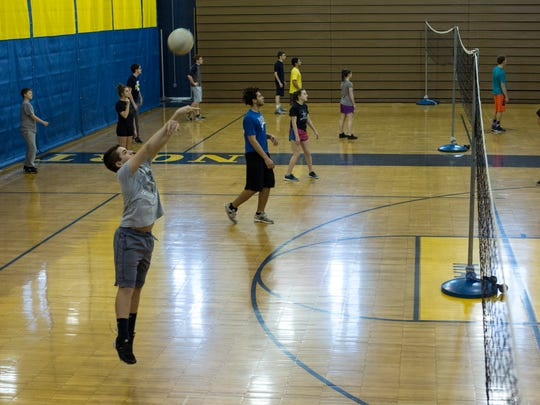 Freshman Dylan Clyne, 15, jumps to hit a volleyball