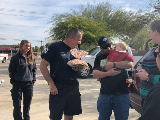 Mesa firefighter Brian Darling met with Ian Fields, his wife Tara and his 9-month-old daughter Ava on Christmas morning in Mesa, Arizona.