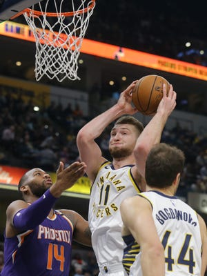 Indiana Pacers center Domantas Sabonis (11) grabs a rebound from Phoenix Suns center Greg Monroe (14) and Indiana Pacers forward Bojan Bogdanovic (44) during a game at Bankers Life Fieldhouse on Jan. 24, 2018.