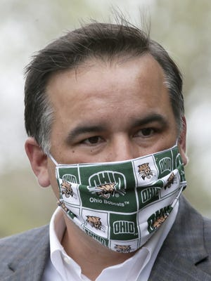 Mayor Andrew J. Ginther, here donning an Ohio University mask, has ordered anyone in public in Columbus to wear a mask. On Monday, the City Council added fines for those who don't.
