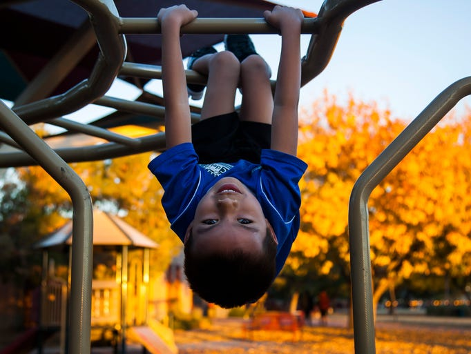 Logan Phillips hangs upside down on monkey bars at Margaret T. Hance Park in 2013. City leaders are looking for new ways to revitalize the park.