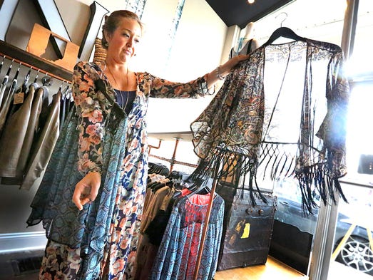 Niche boutique owner Lanie Lopez displays a popular item the shoulder kimono that is part of the trendy Bohemian look. It sells in her Niche shop for $38.