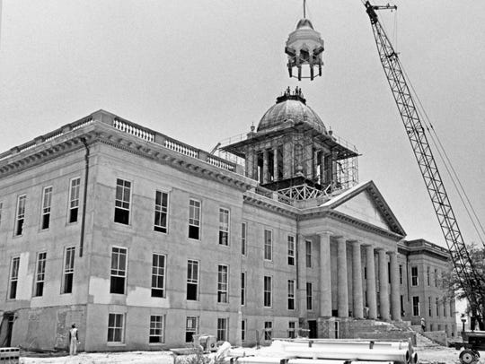 Workers on re-install the dome on Florida's old capitol,