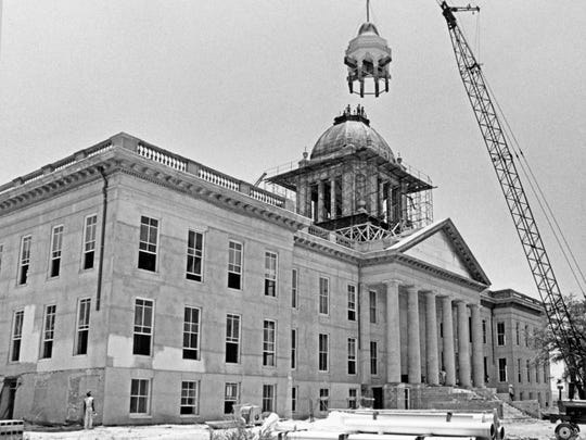 Workers on re-install the dome on Florida's old capitol, which was saved and renovated to its 1902 appearance and today serves as the Florida Historic Capitol Museum.