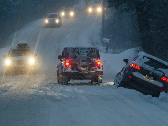 A motorist attempts to pull a car out of the ditch