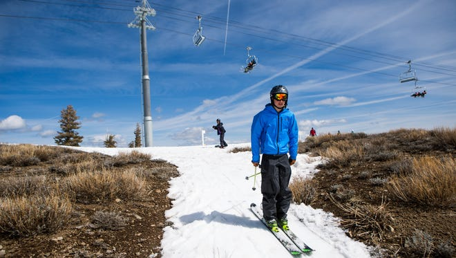 A skier threads his way through patches of dry ground at Squaw Valley Ski Resort, March 21, 2015, in Olympic Valley, Calif. Many Tahoe-area ski resorts have closed due to low snowfall as California's historic drought continues.