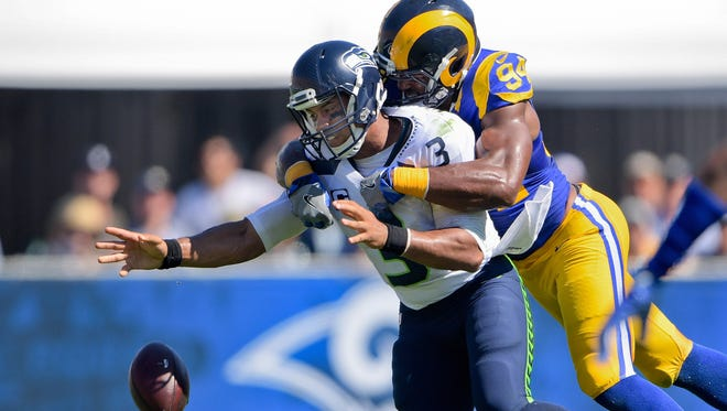 Seattle Seahawks quarterback Russell Wilson (3) looses the ball as he is sacked by Los Angeles Rams defensive end Robert Quinn (94) during the first half of a NFL game against the Seattle Seahawks at Los Angeles Memorial Coliseum.