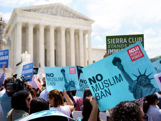 Protesters hold up signs and call out against the Supreme Court ruling upholding President Donald Trump's travel ban outside the the Supreme Court in Washington on Tuesday.