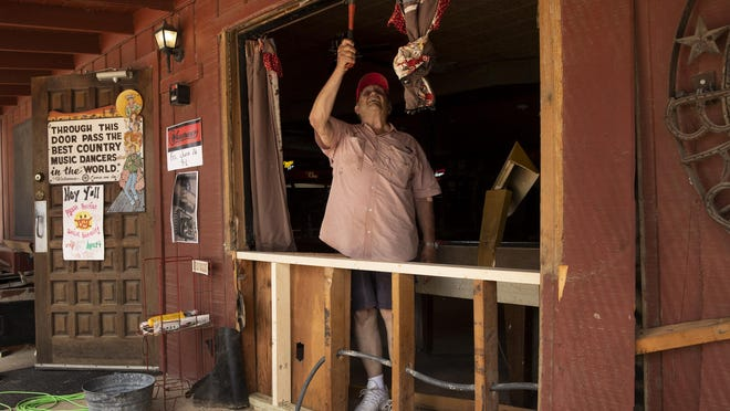Broken Spoke owner James White looks at the damage to the iconic honky-tonk on Tuesday after burglars rammed it with a truck to steal an ATM on the property.