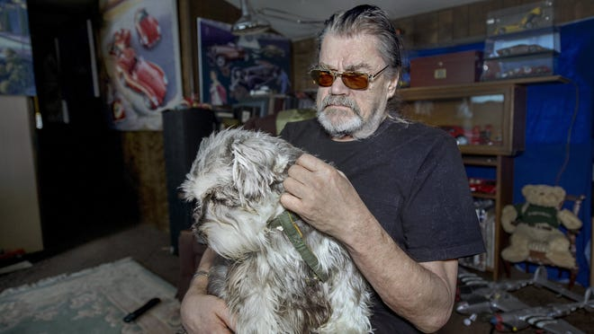 Jack Patrick holds his 7-year-old schnauzer, Andy, in his Warrensburg, Mo., home after receiving a meal and dog food from a Care Connection for Aging Services volunteer. Patrick, who has glaucoma and severe arthritis, receives regular meals through Care Connection, but until recently was sharing them with Andy because he couldn't afford to buy dog food.