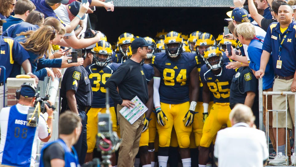 Michigan head coach Jim Harbaugh, center, holds his