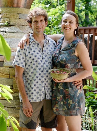Samantha Bowers holds a bowl of freshly picked strawberries from her garden as she stands with her husband, Peter Pfister, at their home in Montford May 24, 2018. Their home will be featured in the GreenWorks Summer Garden Tour.