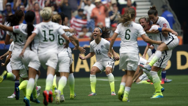 United States midfielder Lauren Holiday (12) celebrates with teammates after defeating Japan in the final of the FIFA 2015 Women's World Cup at BC Place Stadium. United States won 5-2.